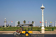 A man driving a tuk tuk is passing a group of flags near the riverside promenade on the Mekong River in Phnom Penh, Cambodia.