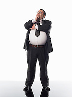 Overweight businessman standing with hand on chin