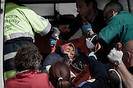 ITALY, Lampedusa : A Tunisian migrant is helped upon arrival at Lampedusa on March 24, 2011. Copyright Christian Minelli.