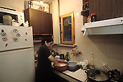 (MODEL RELEASED IMAGE) Melahat Çelik mixes the dough for savory arugula-feta filled Turkish pastries in her apartment kitchen and then will sit on the living room floor and roll paper-thin pastry called yufka around the filling to create an eggroll-style pastry her family loves. (Supporting image from the project Hungry Planet: What the World Eats)