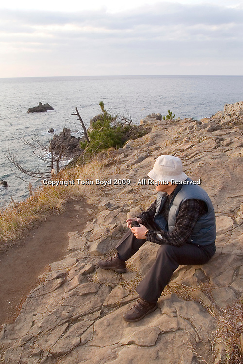 Nov. 26, 2009, Sakai City, Japan: This is 66 year old Isao Saito, a retired police officer from Fukui Prefecture patrolling the rocky cliffs at Tojinbo for possible suicides attempts. He is right at the precipice where many have jumped. Mr. Saito is a member of the NPO suicide prevention group Kokoro ni Hibiku Bunshu Henshukyoku, which was founded by 65 year old Yukio Shige (pronounced shee-gay), a retired policeman from Fukui Prefecture who took up his cause in 2004, just before retirement as a police deputy at a nearby police station. When Shige discovered how many suicides were occurring here, he began patrolling the cliffs of Tojinbo in order to spot those contemplating suicide. Upon retirement Shige opened a small cafe at Tojinbo where he also set up his NPO. Since then other volunteers like Mr. Saito have joined his cause and as of November 2009, he and his group have talked 222 out of committing suicide. They do this by patrolling the cliffs daily with binoculars in hand, and when they spot someone they kindly approach them and coax them away to Shige's cafe where they offer them tea and rice cakes. They also see these people home safely, and in cases where an individual is homeless, they find them accommodations. However there are still some that slip past their watchful eyes and so far in 2009 thirteen people have jumped to their deaths here. Japan has one of the highest suicide rates in the world and 2009 may surpass the record 34,427 deaths that occurred here in 2003. This increase is thought to be a result of the Japanese recession which has been worsened by the global economic downturn. Depression is the number one cause for suicide in Japan, followed by illness and debt. Photo by Torin Boyd.
