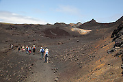 Tourists walk along a trail in the crater of the volcano Sierra Negra, Isabela Island, Galapagos Archipelago - Ecuador.