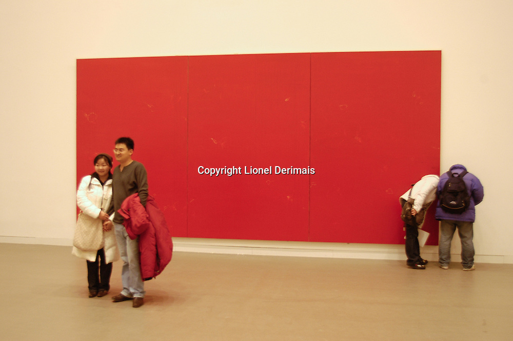 Chinese couple being photographed in front of a red painting in a Beijing museum.