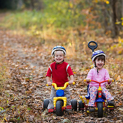 A young boy (age 2) and his sister(age 4) on their  bikes.  Newfields rail trail in Newfields, NH.  Fall.
