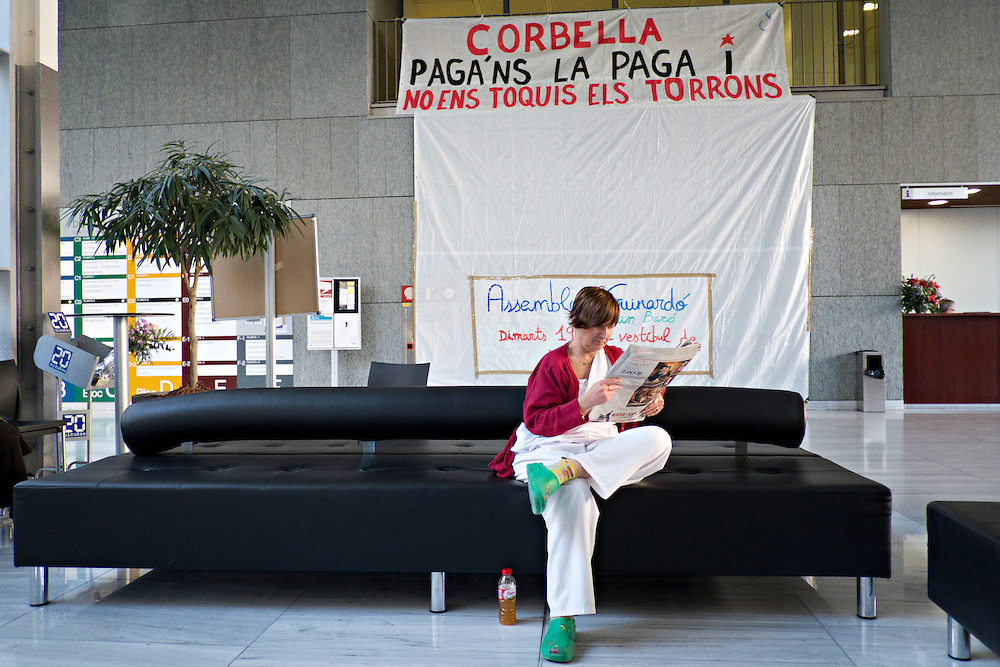 02-01-2013  Sant Pau hospital, Barcelona, Spain. A hospital employee reading the news in front of a banner that reads: 'Corbella pay us and do not touch our nougats'.<br /> <br /> Sant Pau hospital occupation has reached its end. After a 36-day occupation of the hospital hall, the employees decided to dismantle the encampment due to lack of participation. The protest against cuts in the public sector failed to mobilize the bulk of hospital employees.
