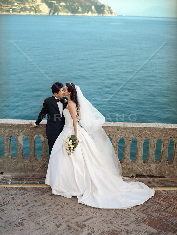 Bride and groom kissing on a patio overlooking the Coast of Italy