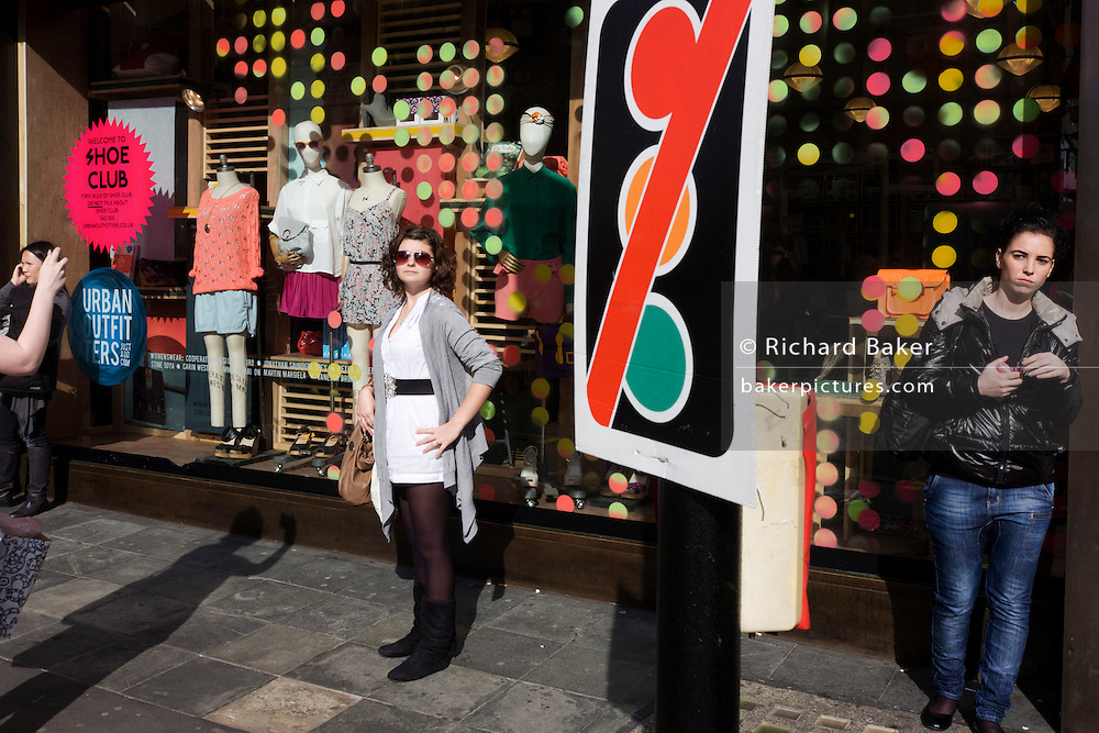 Young woman poses for friend's camera outside the spotted shop window of Urban Outfitters in central London.