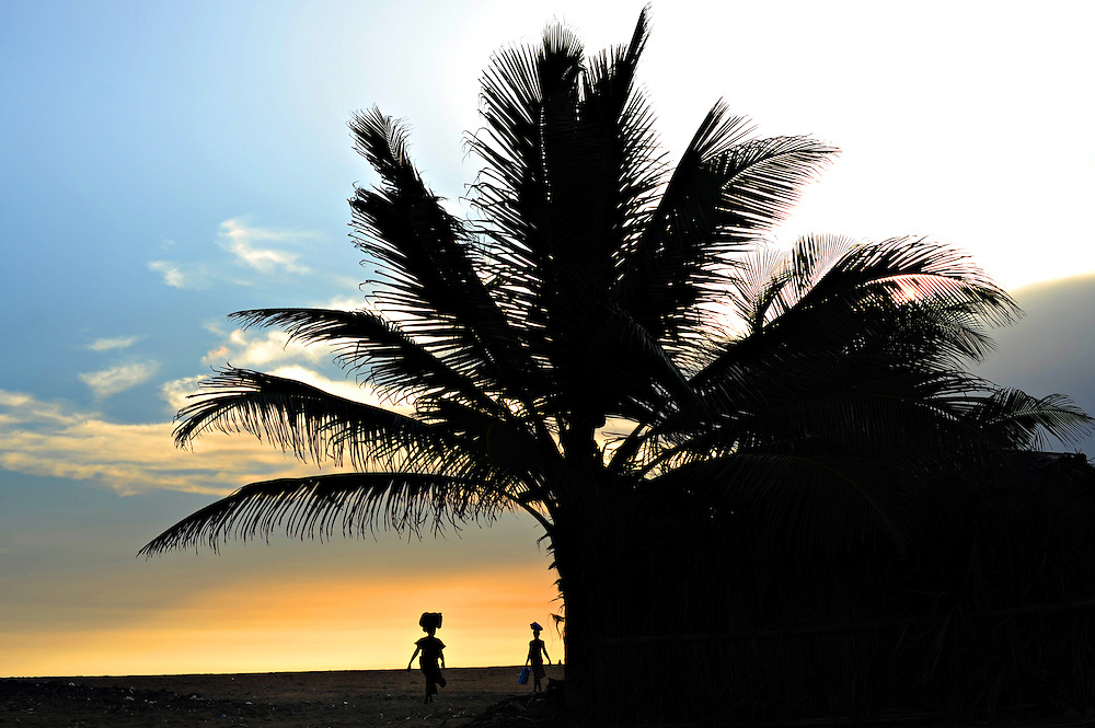GRAND POPO, BENIN - 11-10-16 -  Two women walk along the beach in Grand Popo, Benin at sunset on October 16. Photo by Daniel Hayduk