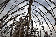 A man constructs a shelter at Kahe IDP site in the town of Kichanga, North Kivu, DRC.