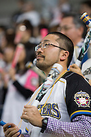 A Japanese man watches a game of his home baseball team- the Hokkaido Nippon Ham Fighters - at the Sapporo Dome in Sapporo, Hokkaido