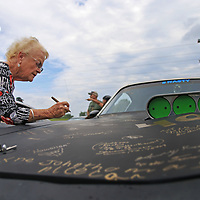 Willie and Clarence Cordell sign the hood of a Trans Am belonging to driver James Thomas and his daughter Beth Woodruff of Austin, Texas. Woodruff says that after getting all of the other drivers to sign the hood, she and her father plan to clear-coat over the signatures in order to immortalize The Bandit Run event.