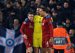 LIVERPOOL, ENGLAND - Tuesday, December 11, 2018: Liverpool's goalkeeper Alisson Becker celebrates with team-mates Andy Robertson (L) and Virgil van Dijk (R) after beating SSC Napoli 1-0 and progressing to the knock-out phase during the UEFA Champions League Group C match between Liverpool FC and SSC Napoli at Anfield. (Pic by David Rawcliffe/Propaganda)