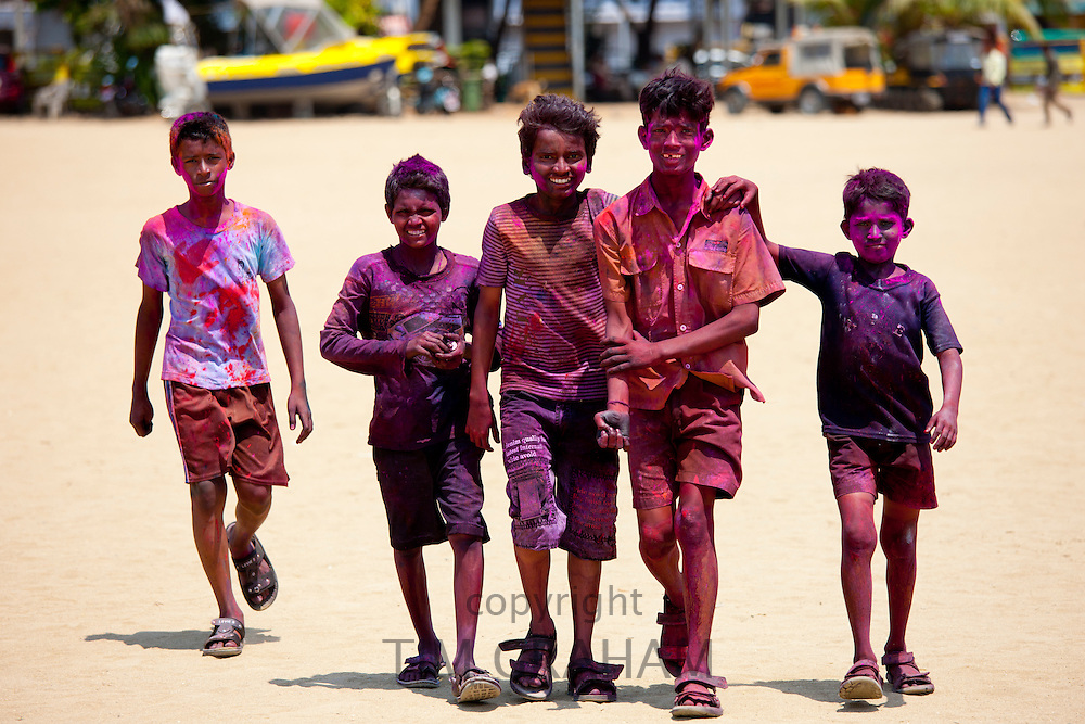 Indian boys celebrating annual Hindu Holi festival of colours smeared with powder paints in Mumbai, formerly Bombay, Maharashtra, India