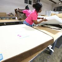 Shaketa Ferrell inserts a foam pad into the shell of a dog bed that is put together for at AbilityWorks in Tupelo to supply every Bed Bath & Beyind across the country.