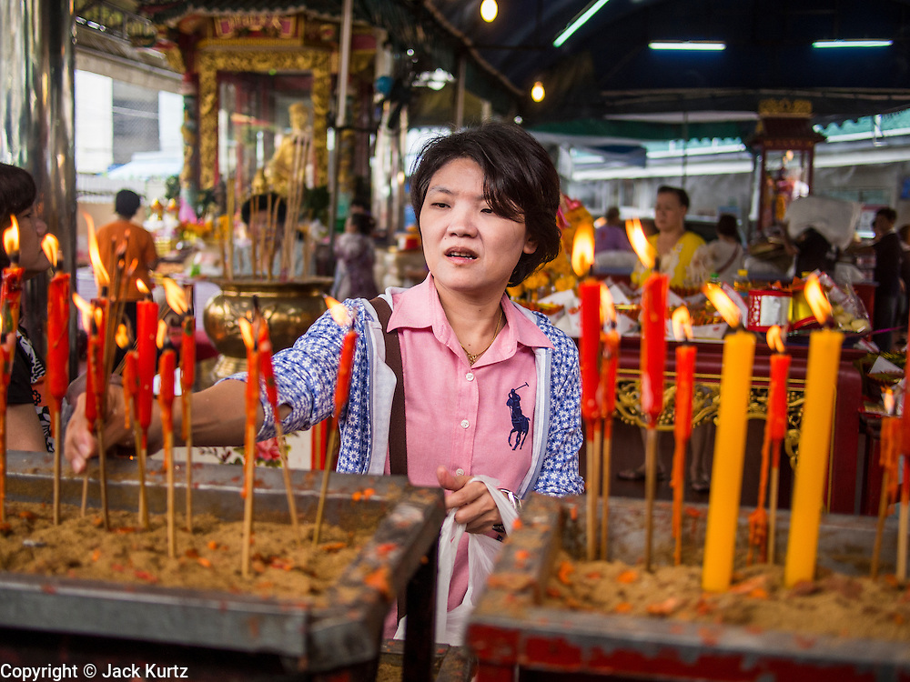 "26 AUGUST 2013 - BANGKOK, THAILAND: A woman lights candles and pray at the Poh Teck Tung Foundation for Hungry Ghost Month in Bangkok. Poh Teck Tung operates hospitals and schools and provides assistance to the poor in Thailand. The seventh lunar month (August - September in 2013) is when the Chinese community believes that hell's gate will open to allow spirits to roam freely in the human world for a month. Many households and temples will hold prayer ceremonies throughout the month-long Hungry Ghost Festival (Phor Thor) to appease the spirits. During the festival, believers will also worship the Tai Su Yeah (King of Hades) in the form of paper effigies which will be ""sent back"" to hell after the effigies are burnt.      PHOTO BY JACK KURTZ"