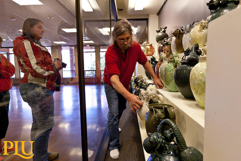 Steve Sobeck setting frog sculptures in place. (Photo/John Froschauer)