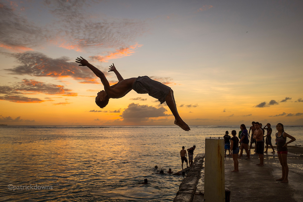 A diver arcs up from a pillar on Sugar Dock, on the beach in Saipan. The dock is a popular local swimming spot on the island.