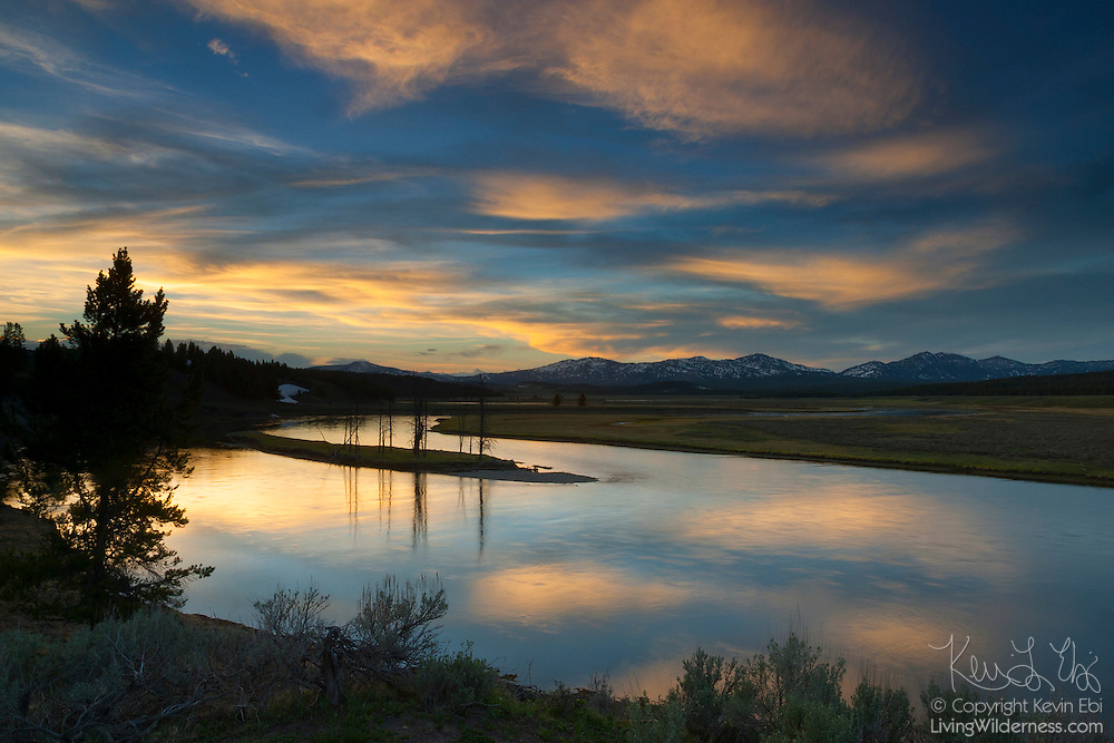 A late spring sunset lights up the sky and reflects in the waters of the Yellowstone River as it winds through the Hayden Valley in Yellowstone National Park, Wyoming.