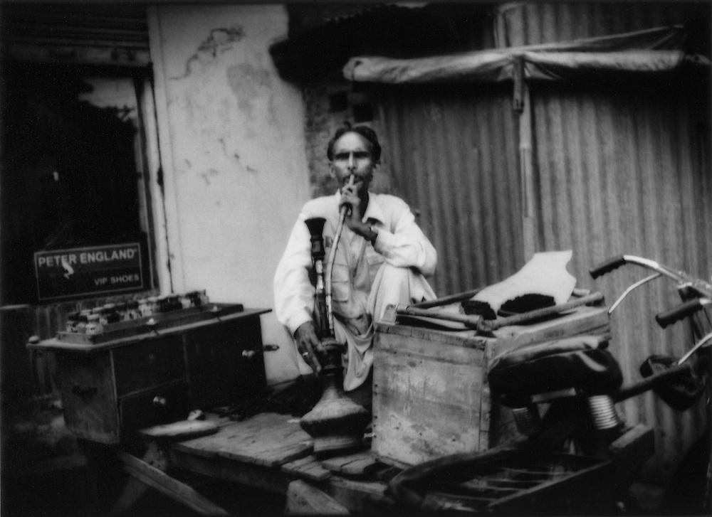Kashmiri shoe repairman smokes a waterpipe while waiting for customers, Srinagar, Indian Administered Kashmir.