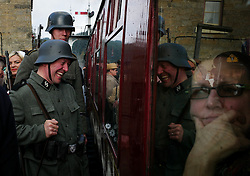 © Licensed to London News Pictures. <br /> 15/10/2016. <br /> Levisham, UK.  <br /> <br /> Re-enactors dressed as German soldiers react to passengers in the train at Levisham station during the North Yorkshire Moors Railway Wartime Weekend event. <br /> The annual event brings together re-enactors and enthusiasts along the length of the NYMR heritage steam railway line to recreate the feel of the war years of the 1940's. <br /> <br /> Photo credit: Ian Forsyth/LNP