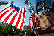 A US Flag suspended between 2 fLadder trucks is reflected in the finish of Bayvilles ladder truck.  Captain Vincent Ungaro died after a long fight with World Trade Center-related leukemia on October 1, 2016.  <br />