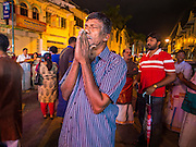 04 OCTOBER 2014 - GEORGE TOWN, PENANG, MALAYSIA: A man prays as the chariot drawn by blessed oxen carries Hindu priests and the Durga deity through the streets of George Town during the Navratri procession. Navratri is a festival dedicated to the worship of the Hindu deity Durga, the most popular incarnation of Devi and one of the main forms of the Goddess Shakti in the Hindu pantheon. The word Navaratri means 'nine nights' in Sanskrit, nava meaning nine and ratri meaning nights. During these nine nights and ten days, nine forms of Shakti/Devi are worshiped.   PHOTO BY JACK KURTZ