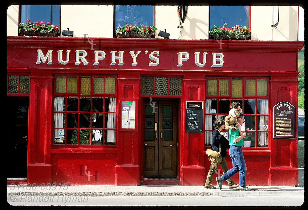 Family walks past Murphy's Pub in town of Dingle on the Dingle Peninsula. Ireland