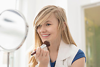 Girl applying makeup in front of mirror at home