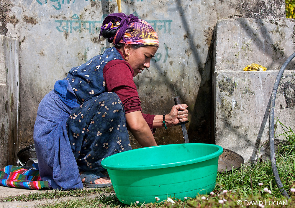 A woman cleaning a pan near her guesthouse in Kutumsang.