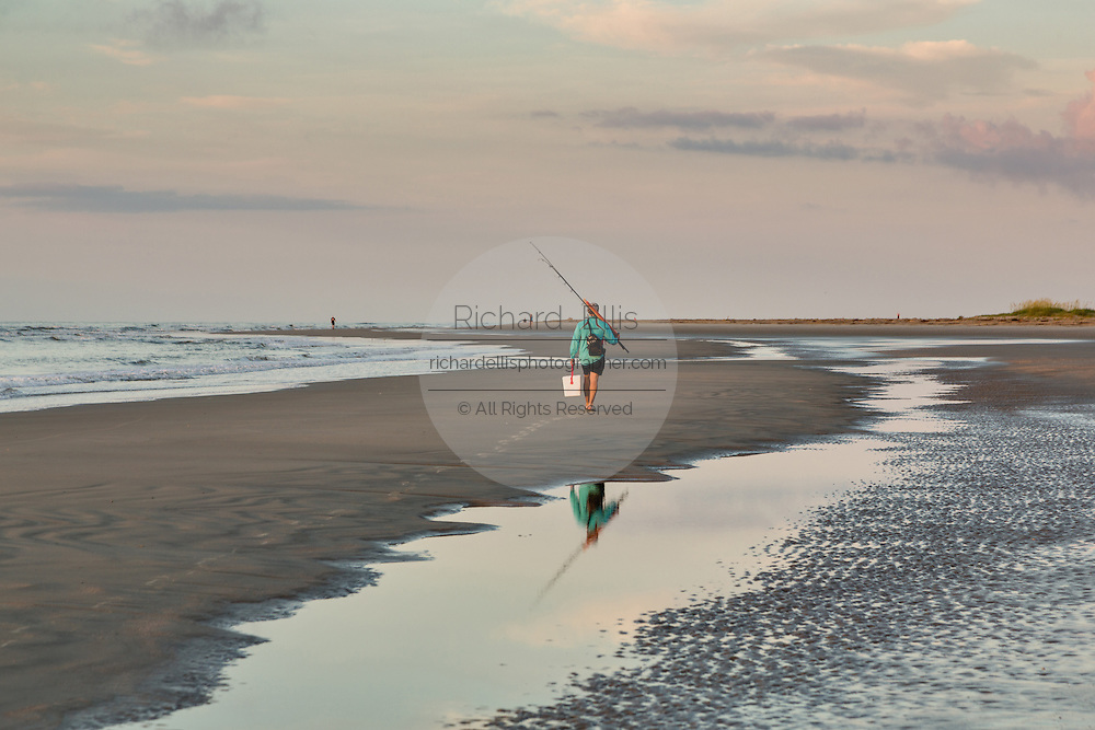 Fishermen walk along the beach at dawn on Isle of Palms at Wild Dunes near Charleston, South Carolina.