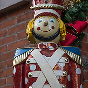 Outdoor Christmas folk art,large wooden toy soldiers on both sides of front door of building.