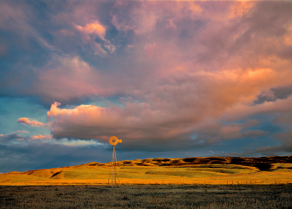 Pink and purple clouds color the sky above a windmill in Ventura County, California.