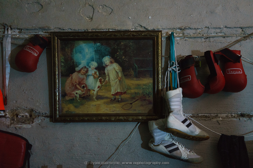 Siyakudumisa Vapi's boxing boots and a couple of pairs of child-sized boxing gloves hang next to a painting on the wall in his room in Johannesburg, South Africa. Currently living in a curtained-off space in the basement of the Hillbrow Boxing Club in one of the city's most notorious neighbourhoods while between jobs, he is training for a fight against the third-ranked fighter in the national featherweight division; if he wins it wil bring him closer to his objective of challenging for the national title, and being able to make a decent living from boxing. Vapi believes boxing pulled him away from the streets and bad company, and gave him discipline.