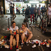 Two young white girls sit in the gutter outside McDonalds eating their dinner after a long day out at the carnival in the sun. The Notting Hill Carnival has been running since 1966 and is every year attended by up to a million people. The carnival is a mix of amazing dance parades and street parties with a distinct Caribbean feel.