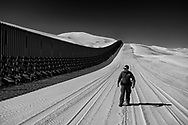 Border Patrol agent Jose Garibay III walks along the sand dunes in Glamis, Caifornia on Wednesday, February 6, 2019. The fencing along the dunes is not secured into the ground because of the constantly shifting sand(Photo by Sandy Huffaker for The Wall Street Journal)<br /> BORDER<br /> 54309
