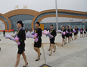 HECHI, CHINA - (CHINA OUT) <br /> <br /> Airport in The Mountains  <br /> <br /> Airline stewardesses holding flowers to celebrate a successful route-proving flight at Hechi Jin Cheng Jiang Airport on July 10, 2014 in Hechi, Guangxi Zhuang autonomous region of China. Hechi Jin Cheng Jiang Airport, a 4621 squremeters airport, with the investment of 850 millions RMB (about 136 millions USD) was built on the altitude of 677 meters. The airport which has a 2500 square meters parking lot will open to air traffic in August with an air route of Haikou-Hechi-Chongqing.<br /> ©Exclusivepix