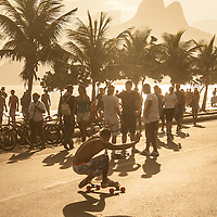 Man performs a trick on his skateboard in front of some other young people on a road in Rio De Janerio.