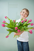 Smiling boy holding out tulip flowers against gray background