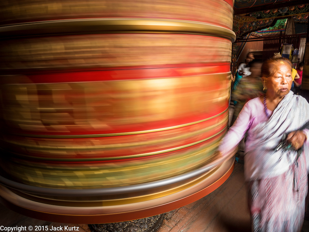 31 JULY 2015 - KATHMANDU, NEPAL: A woman spins a prayer wheel in a Tibetan monastery near Bodhnath Stupa. Bodhnath Stupa in the Bouda section of Kathmandu is one of the most revered and oldest Buddhist stupas in Nepal. The area has emerged as the center of the Tibetan refugee community in Kathmandu. On full moon nights thousands of Nepali and Tibetan Buddhists come to the stupa and participate in processions around the stupa. The stupa was heavily damaged in the earthquake of 25 April 2015 and people are no longer allowed to climb on the stupa, now they walk around the base and pray with butter lamps.   PHOTO BY JACK KURTZ