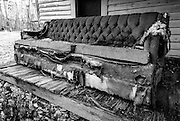 A tattered, decrepit couch on the porch of this abandoned house near the High Rock Dam in Denton, NC.g