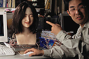 Student Yousuke Kato points to a female face robot created at the Science University of Tokyo, Japan, Fumio Hara Robotics Lab. The female face robot (secondgeneration) has shape-memory electric actuators that move beneath the robots' silicon skin to change the face into different facial expressions much as muscles do in the human face. The research robot undergoes a metamorphosis with each class of students assigned to work on it. The latest iteration allows the robot's face to mold into six different expressions: happiness, sadness, fear, disgust, anger, and surprise. In some images, the computer monitor displays a graphical representation of the software creating the expression on the robot.