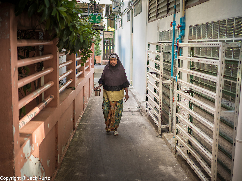 10 JULY 2015 - BANGKOK, THAILAND: A woman walks to Haroon Mosque in Bangkok before Iftar. Iftar is the evening meal when Muslims end their daily Ramadan fast at sunset. Iftar is a communal event at Haroon Mosque and hundreds of people usually attend the meal.     PHOTO BY JACK KURTZ