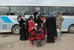Licensed to London News Pictures. 10/11/2016. Mosul, Iraq. A young girl looks back she and other families, escaping from areas within the city where fighting between Iraqi Security Forces and Islamic State militants is taking place, board a bus in the city's Gogjali District. The bus, provided by the Iraqi Army, will take them to the safety of a refugee camp in Iraqi-Kurdistan.<br /> <br /> The battle to retake Mosul, which fell June 2014, started on the 16th of October 2016 with Iraqi Security Forces eventually reaching the city on the 1st of November. Since then elements of the Iraq Army and Police have succeeded in pushing into the city and retaking several neighbourhoods allowing civilians living there to be evacuated - though many more remain trapped within Mosul. Photo credit: Matt Cetti-Roberts/LNP