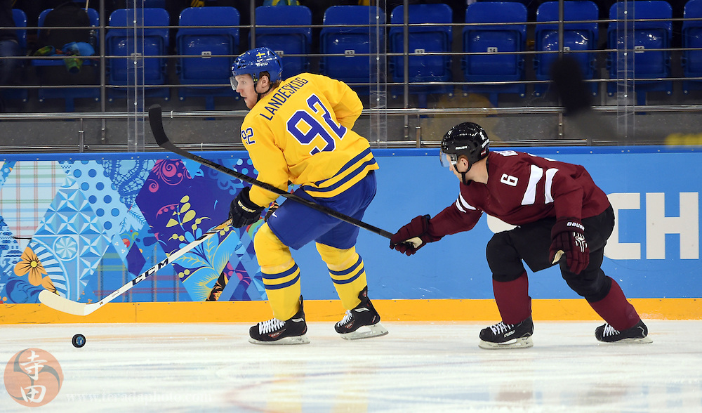 Feb 15, 2014; Sochi, RUSSIA; Sweden forward Gabriel Landeskog (92) controls the puck against Latvia defenseman Arvids Rekis (6) in a men's preliminary round ice hockey game during the Sochi 2014 Olympic Winter Games at Shayba Arena.