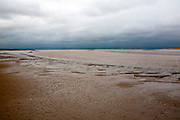 Muddy channel of the River Parrett at low tide near its mouth at Burnham on Sea, Somerset, England