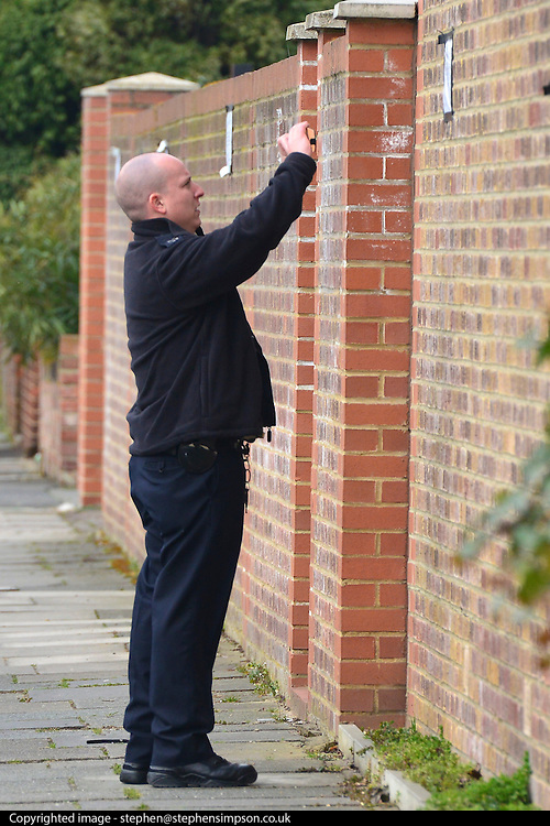 © Licensed to London News Pictures. 08/04/2013. London, UK A police man photographs a sign asking people not to park there on the 9th April on the wall of the The North Korean Embassy in Ealing in West London today, 8th April 2013. The Embassy is based in a 1920's detached house in a residential area. Tensions are high between countries around the world and the North Koreans. Photo credit : Stephen Simpson/LNP