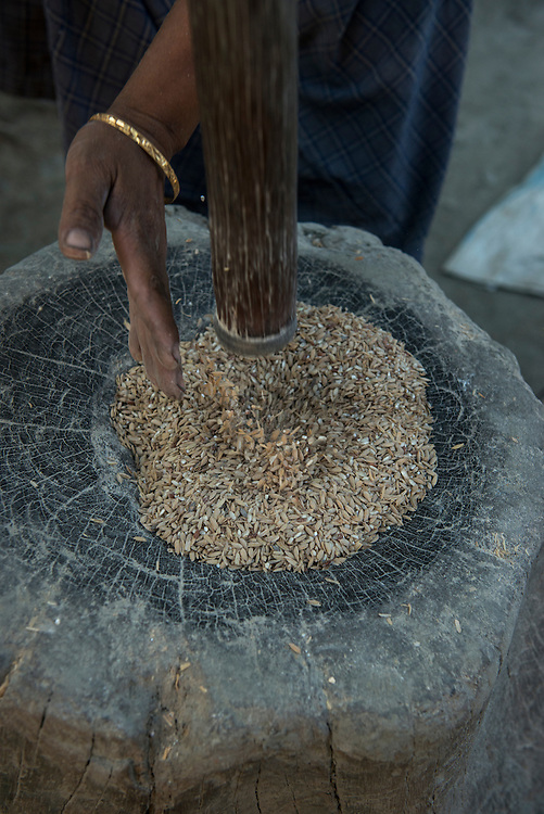 Mising pounding rice<br /> Mising Tribe (Mishing or Miri Tribe)<br /> Majuli Island, Brahmaputra River<br /> Largest river island in India<br /> Assam,  ne India