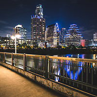 Austin skyline at night with a bridge railing along the colorado river. Austin is a major city in the Southwestern United States of America. Photo was taken in 2016. © Paul Velgos with All Rights Reserved.