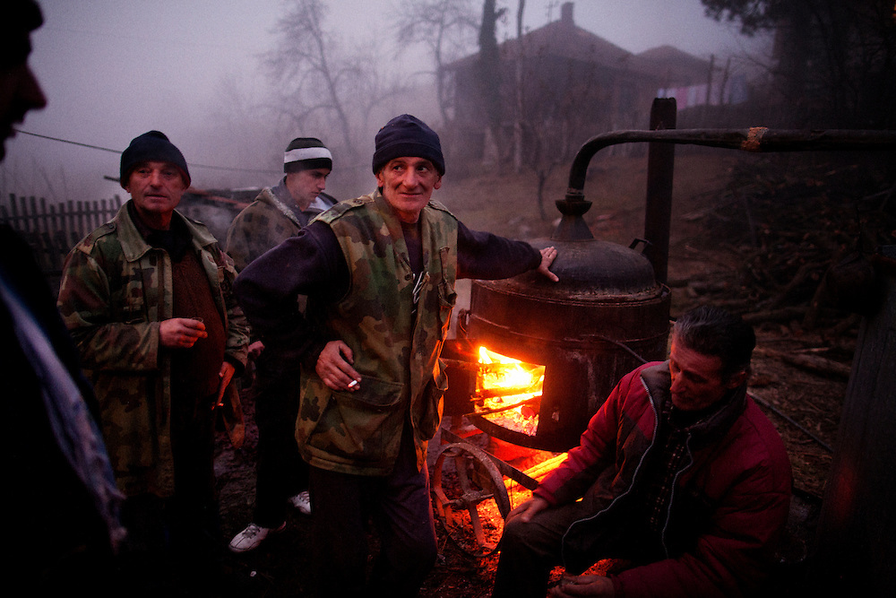 Men gather next to the wood and corn-fired still while producing traditional Serbian plum brandy...Rakija Production in Trudelj, Serbia in late November 2011.