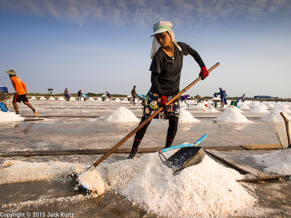09 MARCH 2015 - NA KHOK, SAMUT SAKHON, THAILAND: A Burmese migrant worker on a salt farm near Samut Sakhon, Thailand, rakes salt into mounds during the salt harvest. The coastal provinces of Samut Sakhon and Samut Songkhram, about 60 miles from Bangkok, are the center of Thailand's sea salt industry. Salt farmers harvest salt from the waters of the Gulf of Siam by flooding fields and then letting them dry through evaporation, leaving a crust of salt behind. Salt is harvested through dry season, usually February to April. The 2014 salt harvest went well into May because the dry season lasted longer than normal. Last year's harvest resulted in a surplus of salt, driving prices down. Some warehouses are still storing salt from last year. It's been very dry so far this year and the 2015 harvest is running ahead of last year's bumper crop. One salt farmer said prices are down about 15 percent from last year.    PHOTO BY JACK KURTZ